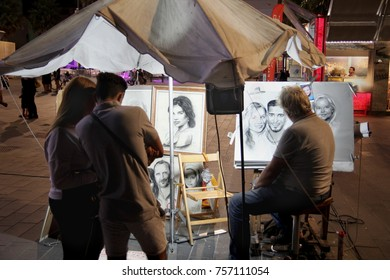 Cap D'Agde, Herault, France - August 30 2017: A street artist working in charcoal and chalk draws a portrait of a young couple while they watch, in the port town of Cap D'Agde, Languedoc, France