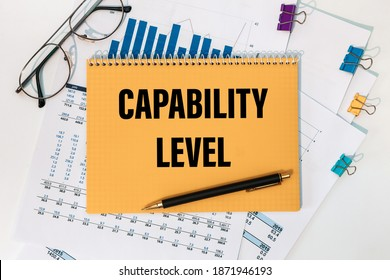 Capability level is written on a notepad on an office desk with office accessories.