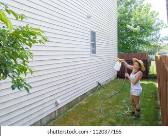 Capable fit attractive woman in a straw hat standing on the lawn spraying down the house sidings with a handheld pressure sprayer on a hosepipe