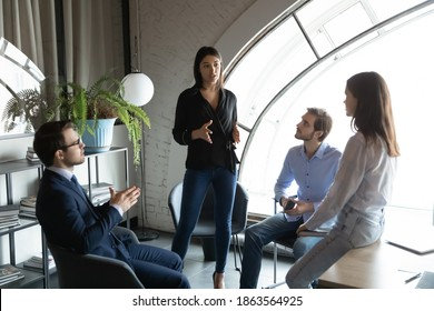 Capable qualified indian female business trainer coach explain learning material to diverse group of young students interns colleagues on intensive course workshop seminar in office or coworking space