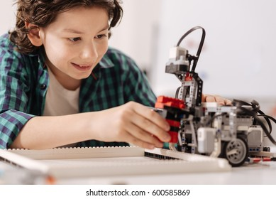 Capable teen kid constructing robot in the studio