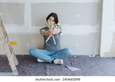 Capable young woman showing off a handful of paintbrushes as she relaxes on the floor on site in a new build home in front of an unfinished wall in a decorating concept