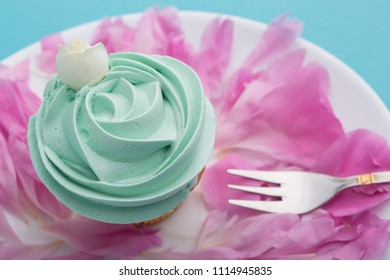 capcake on a white plate with pink petals of flowers on a turquoise background, holiday or wedding concept