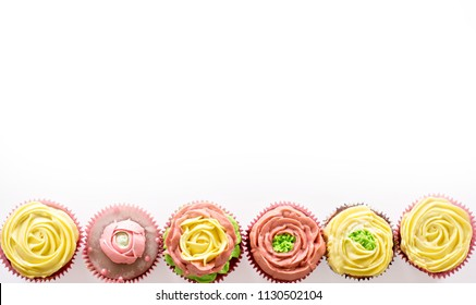 Capcake with yellow and pink cream on a white background. Isolate.