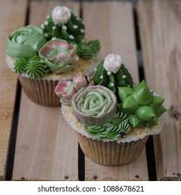 Capcakes decorated with creamy succulents on a wooden background