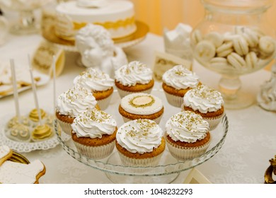 capcakes with white cream and golden peas on a glass dish