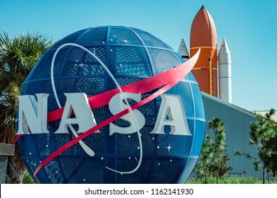 Cape Canaveral, Florida - August 13, 2018: NASA globe with space shuttle booster rocket in backgrond at NASA Kennedy Space Center