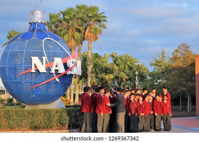 Cape Canaveral FL/USA: December 10, 2018 – Male students from India prepare to pose for photo in school uniforms at sunset at iconic NASA globe during Christmas season at Kennedy Space Center.