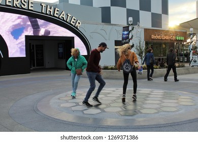 Cape Canaveral FL/USA: December 10, 2018 – Visitors dance at dusk on randomly lighted circles in sidewalk outside Universe Theater, Rocket Garden Café, and The Space Shop at Kennedy Space Center.