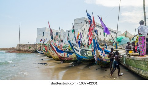 Cape Coast, Ghana - February 15, 2014: Colorful moored wooden fishing boats in African harbor town Cape Coast with colonial castle in background