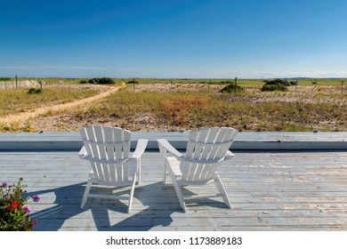 Cape Cod beach at sunset with beach chairs on, Cape Cod, Massachusetts, USA.