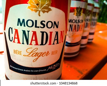 CAPE COD, MASSACHUSETTS, USA: JULY 20, 2016: A MACRO FOCUSED SHOT OF A CAN OF MOLSON CANADIAN BEER IN THE FOREGROUND AND ROW OF THE SAME CANS OUT OF FOCUS IN THE BACKGROUND.