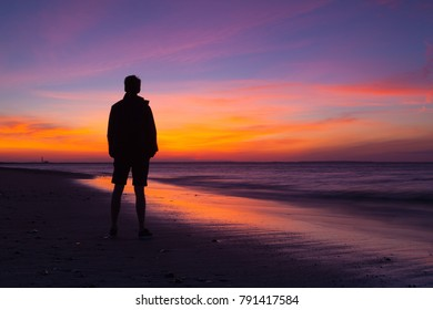 Cape Cod,Massachusetts, USA - July 13,2016: Lonely man on the empty beach at dramatic sunset. Cape Cod, USA
