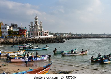Cape Comorin (Kanyakumari), India, West Bengal (Tamil Nadu), March, 15, 2019. Fisherfolk on fishing boats from the beach and St. Arockia Nathar Church ion cape Comorin (Kanyakumari), India, Tamil Nadu