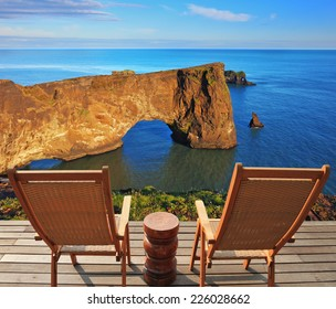 Cape Dirholaey in southern Iceland in July. The colossal rock lit summer sunset. On a coastal rock delivered comfortable wooden loungers