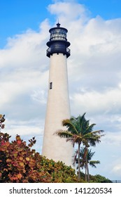 Cape Florida Light lighthouse with Atlantic Ocean and palm tree at beach in Miami with blue sky and cloud.