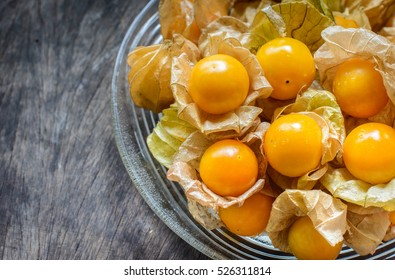 Cape gooseberry (Physalis Peruviana) on a glass plate putting on a wood table - plant species of the genus Physalis, originally from Peru, but cultivated in the region of the Cape of Good Hope, Africa