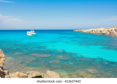 CAPE GRECO AREA, CYPRUS, APR 11, 2016: White yacht with tourists in a paradise small lagoon with clear cyan water and white sand in underworld in Cape Greco National Park on Cyprus.