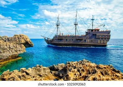 CAPE GRECO,AYA NAPA, CYPRUS - OCTOBER 24, 2017: Pleasure craft on the Mediterranean sea .Tourists in the Pirate ship. Pirate ship sailing near famous Bridge of Love near Ayia Napa.