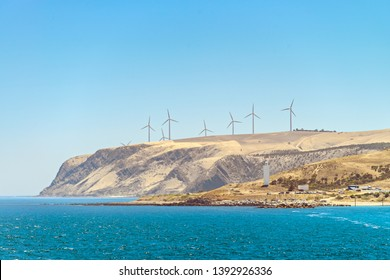 Cape Jervis windmills and lighthouse viewed from departing ferry, Fleurieu Peninsula, South Australia
