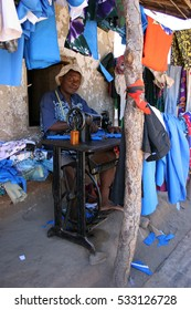 CAPE MACLEAR, MALAWI - 2 MAY 2016: An informal trader displays his wares while sewing new garments in his shop. It is estimated that the informal economy covers 89% of Malawi's labour force. Editorial