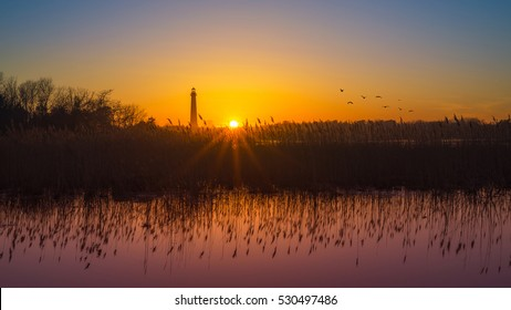 Cape May lighthouse sunset with phragmites reflecting in the marsh.