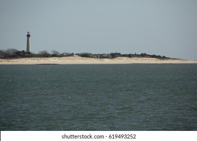 CAPE MAY, NEW JERSEY, USA - MARCH 7, 2017: Cape May Lighthouse and sand dunes with cottages awaiting another summer season at Cape May Point in southern New Jersey.