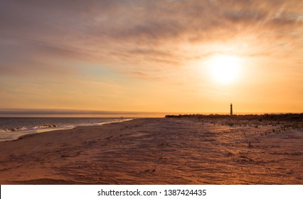 Cape May NJ lighthouse at sunset in early spring Atlantic Ocean with warm soft light