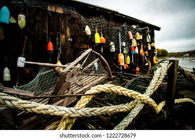Cape Neddick, Maine, USA: October 21st, 2018: Old broken wooden lobster traps and maritime rope lay in a pile in focus with the Cape Neddick Lobster Pound out of focus in the background.