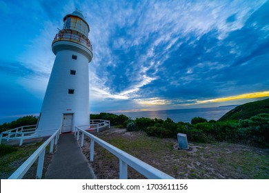 Cape Otway historic lighthouse shadowy and moody on southern point of Australiaunder dramtic sky at sunset in state of Victoria.