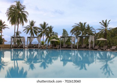 Cape panwa, puket Thailand - May 16,2017 : outdoor swimming pool. Wooden beach chairs beside outdoor swimming pool. Atmosphere of sunset time at outdoor swimming pool.