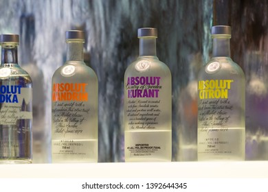 Cape Town - April 28, 2019: close up of variety of bottles of Absolut flavoured vodka  lined up in a row on a bar counter top in front of a waterfall flowing down a glass wall