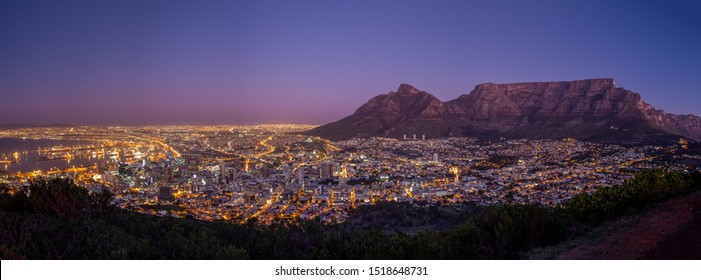 Cape Town during blue hour in front of the landmark Table Mountain. Stunning purple sky complements the illuminated cityscape.