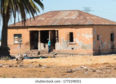 Cape Town - February 12, 2020:  poor living conditions showing poverty in daily life in an urban environment in South Africa as a man stands outside an old run down and neglected house