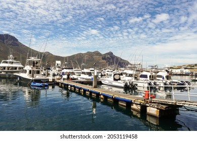 Cape Town - February 17, 2021:  view of Hout Bay marina and boats moored at the jetty with selective focus on the boat called Beluga and the mountain or Chapmans Peak Drive in the background