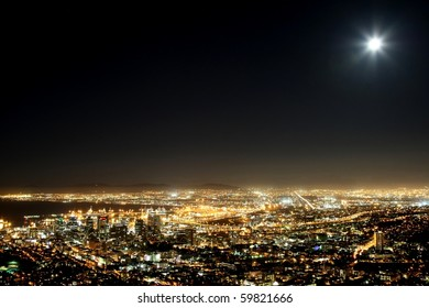 Cape Town harbor and city at night with moon in the sky