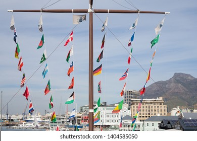 Cape Town - May 07, 2019:  large or huge wooden masthead displays rows or lines of international flags of countries of the world in a central area overlooking buildings and the sea at V&A Waterfront