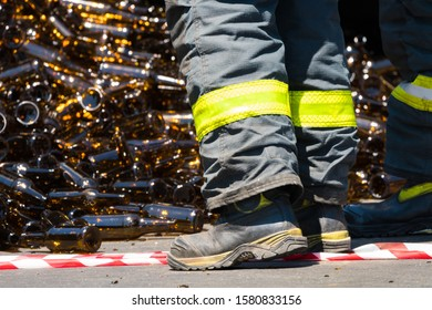 Cape Town - November 29, 2019:  emergency worker or fireman clears away a spill of glass bottles that litter the road during an accident, he wears heavy duty work boots and high visibility clothing
