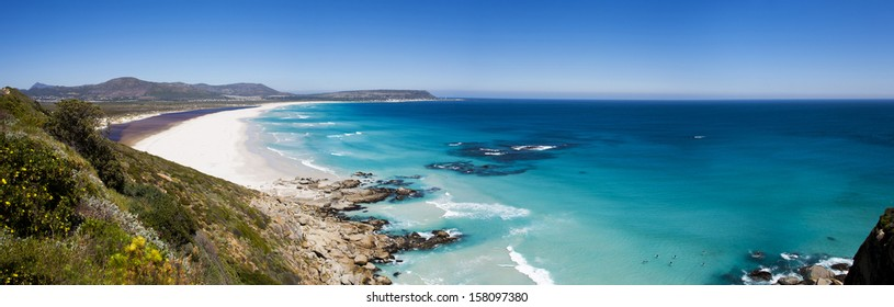 Cape Town - panoramic aerial view of surfers at beautiful Noordhoek Beach