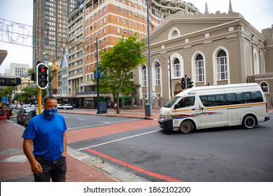 Cape Town, South Africa - 11-23-20   Cloudy day in Cape Town. Man with wearing blue t-shirt and face-mask walking by. Taxi in background.