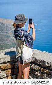 Cape Town, South Africa, 2nd October 2017 Ethnic female tourist taking photos with phone camera of views from Table mountain