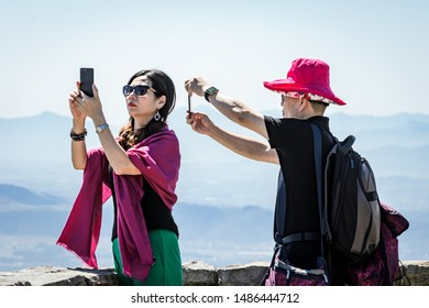 Cape Town, South Africa, 2nd October 2017 Ethnic male and female tourists taking photos with phone cameras of views from Table mountain