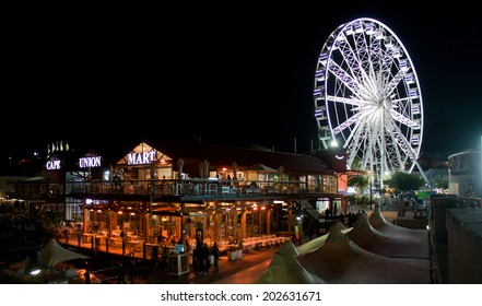 CAPE TOWN, SOUTH AFRICA - APRIL 2. 2014: Night photo of the popular restaurant strip and Ferris wheel at Cape Town harbor front.