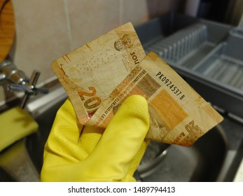 Cape Town, South Africa - Aug 6, 2019: Domestic worker holds twenty South African Rand note, the minimum hourly wage for workers in South Africa since January 1, 2019 (National Minimum Wage Bill).