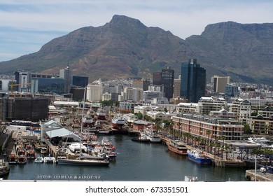 CAPE TOWN, SOUTH AFRICA - CIRCA NOVEMBER 2016: Boats moored in the harbor at the V&A Waterfront, seen from above, with the city and Table Mountain beyond