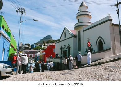 CAPE TOWN, SOUTH AFRICA - CIRCA OCTOBER 2017: Muslim residents gathering on the street in front of a mosque in Bo-Kaap (former Malay Quarter) in central Cape Town.
