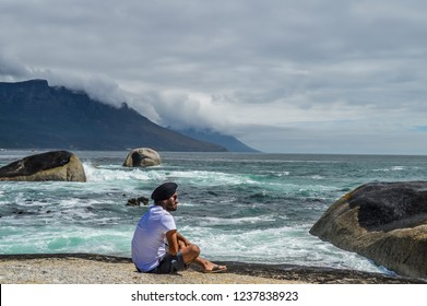 Cape Town , South Africa - Dec 16 2016:An Indian Punjabi adult male with Turban giving a side pose for me on a rock on Maiden's cove beach near Camp's bay beach
