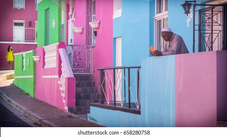 Cape Town, South Africa - December 28th 2016. An old man reading a book and a fashioned girl walking around in Bo-Kaap district.