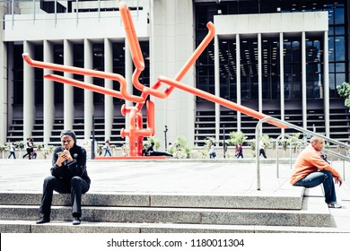 Cape Town, South Africa, February 9, 2018: People resting on steps in front of the Knot - modern art sculpture near Civic Centre in Cape Town