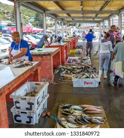 Cape Town, South Africa - February 27, 2019: unidentified fresh fish vendors at the fish market in the Kalk Bay Harbour sell the daily catch image in portrait format